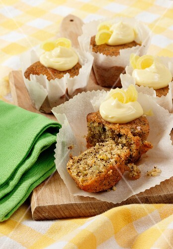 Several Seeded Lemon drizzle cupcakes in white paper cupcake cases on a wooden board