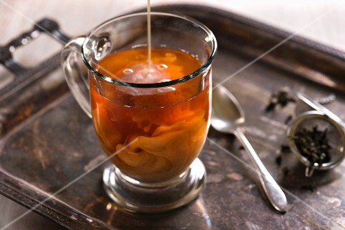 A glass of tea with milk pouring in and swirling. Antique, rustic styling with light background