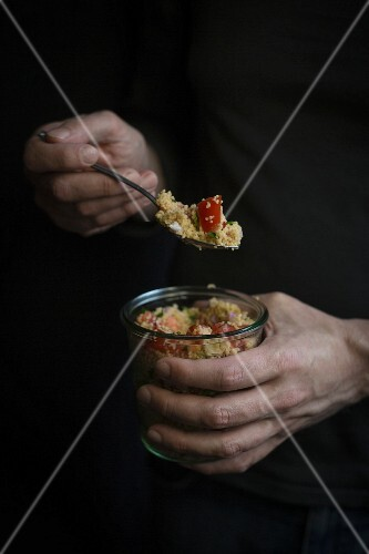 Hands holding a jar of couscous before dark background