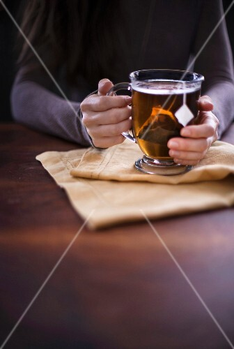 Woman holding a cup of hot tea sitting on linen and a dark wood surface