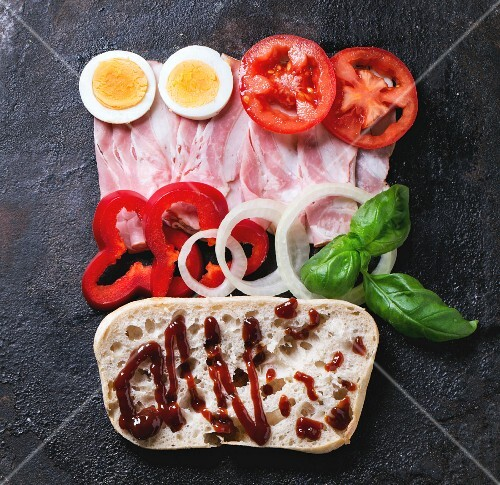 Ingredients for sandwich with ham, eggs, vegetables and ketchup over black background