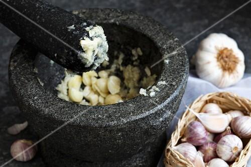 Mashed garlic in grey granite mortar with pestle, standing on dark sheet metal