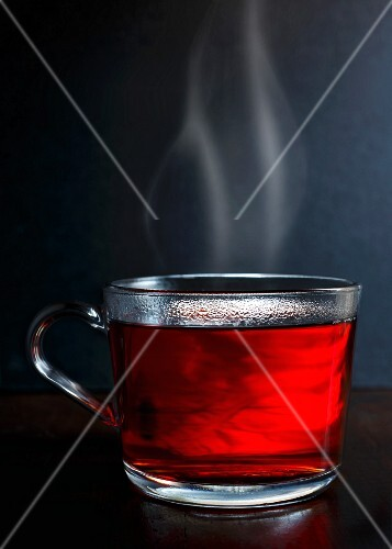 Hot red berry fruit tea in a glass mug with steam standing on a dark wood with dark grey background