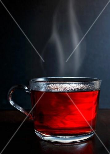 Dampfender roter Beerenfrüchtetee in Glastasse