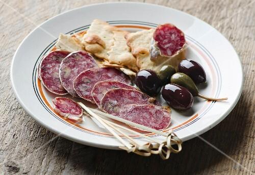 Salami mit Oliven und Cräckern auf weißem Teller