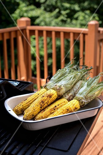 A large plate full of grilled corn on the cob on a table outdoors