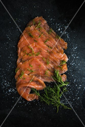 Slices of smoked salmon with sea salt flakes and dill