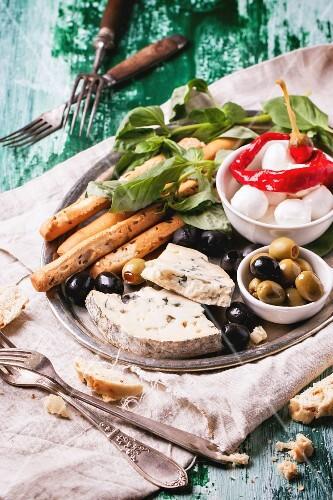 Gemischte Antipasti Blauschimmelkäse, Oliven und Mozarella serviert auf silbernen Tablett an grünem Holztisch