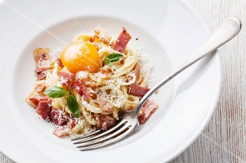 Spaghetti Carbonara on white plate with ham and yolk