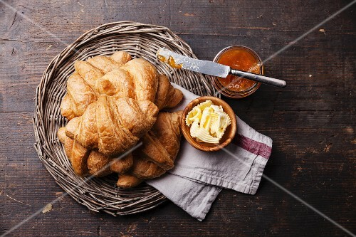 Croissants with butter and jam in wicker tray on dark wooden background
