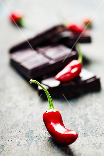 Dark chocolate with chili pepper over wooden background