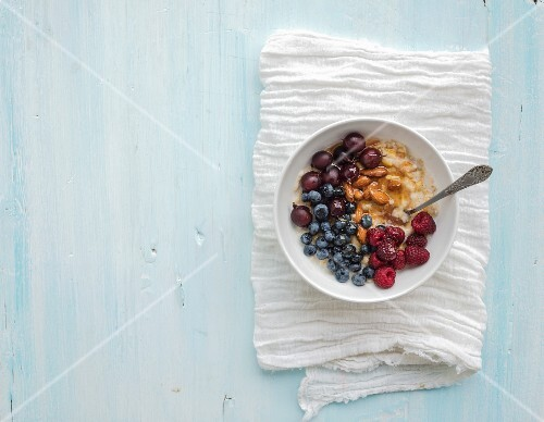 Healthy breakfast set. Bowl of oat porridge with fresh berries, almond and honey over white napkin