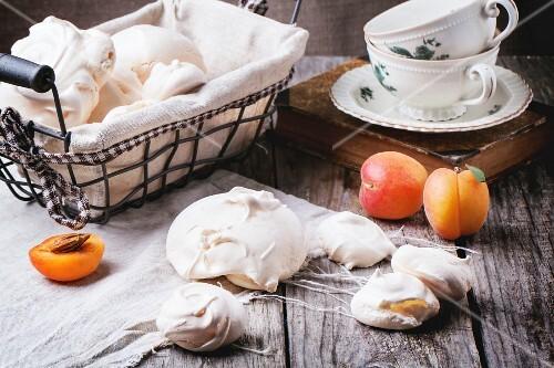 Selbst gemachte Baiser, serviert mit Aprikosen, und Teetassen auf Holztisch