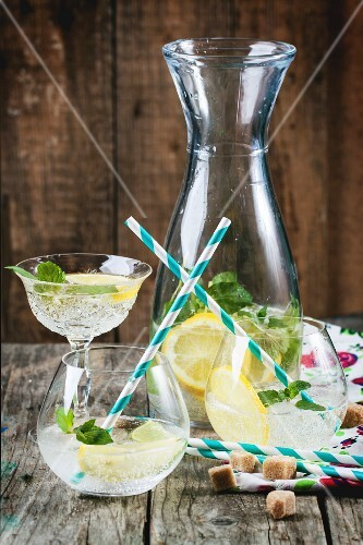 Frische hausgemachte Limonade mit Zitrone, Limette und Minze in Gläsern mit Strohhalm auf Holztisch