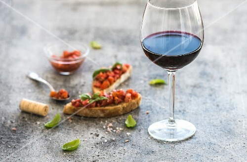 Glass of red wine and canapes with tomatoes and basil