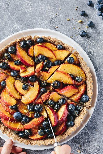 A woman is slicing a peach and blueberry tart with a knife