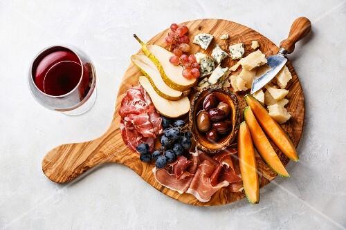 antipasti platte mit schinken k se obst und oliven dazu ein glas rotwein bild kaufen. Black Bedroom Furniture Sets. Home Design Ideas