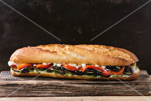 Vegetarian baguette submarine sandwich with grilled eggplant, pepper and feta cheese on wooden chopping board