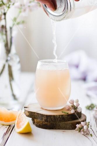 Pink Grapefruit Cocktail wird in Glas gegossen