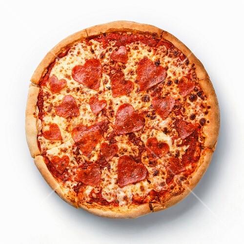 Ganze Pepperoni-Pizza mit Salami in Herzform auf weißem Hintergrund