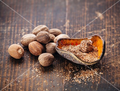 Grated nutmeg on dark wooden background