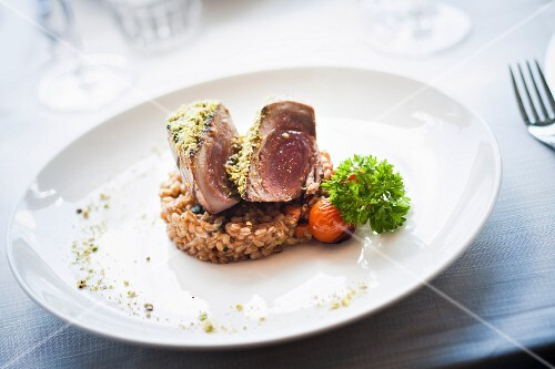Tuna in a pistachio crust on a bed of spelt and vegetables