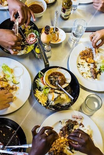 Lunch im Restaurant mit Rindfleischeintopf, Hähnchen und Fisch (Südafrika)