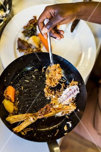 Reste von gebratenem Fisch mit Naturreis und Gemüse in Pfanne (Südafrika)