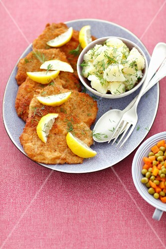 Pork schnitzels with potatoes, carrots and peas