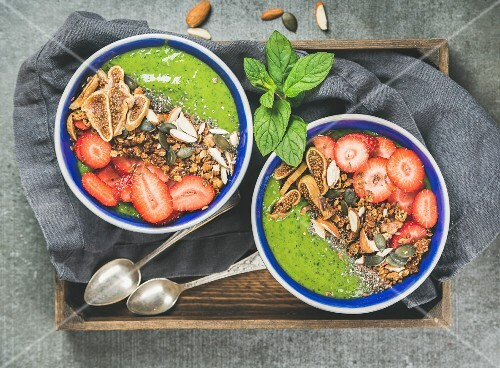Green smoothie bowls with strawberries, granola, chia and pumpkin seeds, dried figs and nut in wooden tray