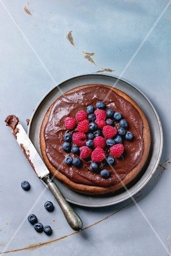 Chocolate cake with fresh berries and chocolate cream, served with vintage knife