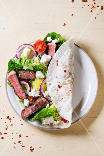 Overhead view on plate with taco with feta cheese and beef over white wooden background