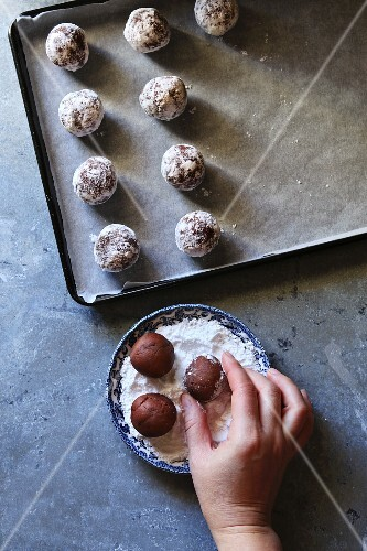 Making chocolate crinkle cookies.Female hand coating dough ball with icing sugar, top view