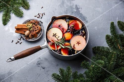 Glühwein mit Orangen, Äpfeln und Gewürzen in Aluminiumtopf