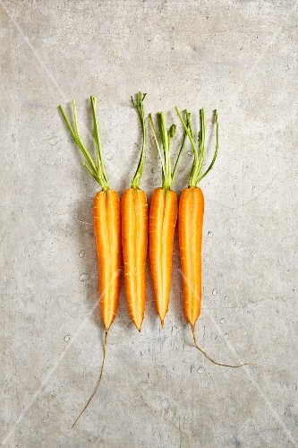 Four carrots cut in half longways, on a grey background (seen from above)