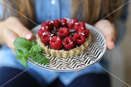 Vegan tart with chocolate avocado banana mousse and raspberries
