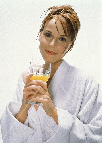 Young woman in bathrobe with a glass of orange juice