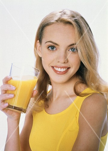 Young blond woman with a glass of orange juice