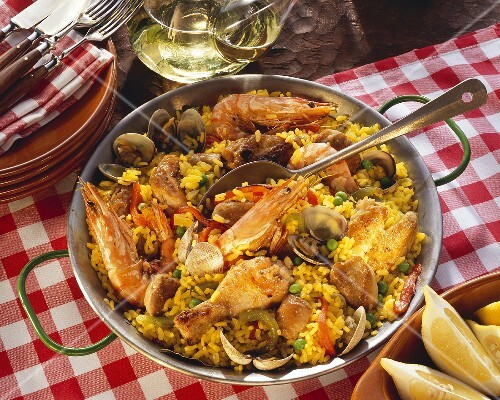 Paella with meat and seafood in pan