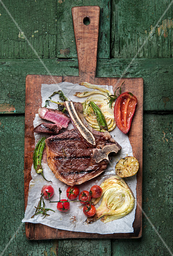 A grilled club steak with vegetables on a chopping board