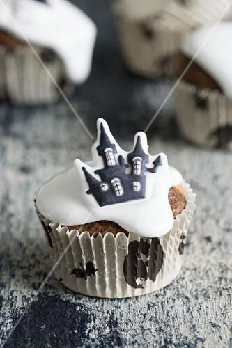 A chocolate muffin decorated with icing and a haunted house for Halloween