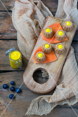 Vegetarian sweet jelly appetizer on pieces of papaya garnished by yellow sauce placed on wooden board beside blueberries