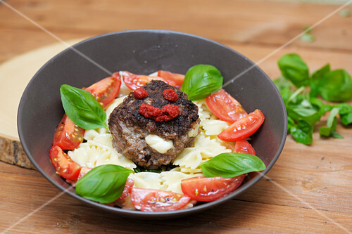 Minced meat steaks with mozzarella served with farfalle and a tomato salad