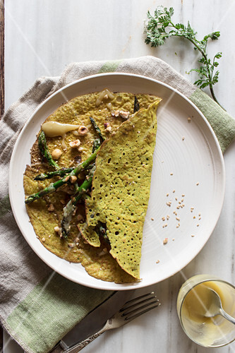 Top view of white plate with oat crepe with asparagus and tahini paste served on rustic board with greens
