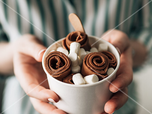 Rolled Chocolate ice cream in cone cup in woman hands