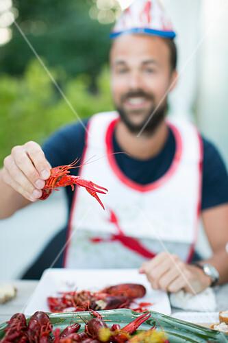 Mid adult man holding crayfish, Stockholm, Sweden