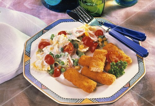 Chicken fingers with pasta & vegetable salad on plate
