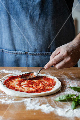 Anonymous chef smearing fresh tomato sauce on raw dough while cooking pizza on table