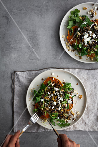 Overhead anonymous person adding ingredients to tasty baked sweet potato salad while preparing lunch over gray table