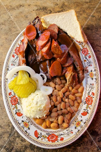 Barbecue ribs, sausage with beans mashed potatoes white bread onion and pickle cucumber, Texas, USA